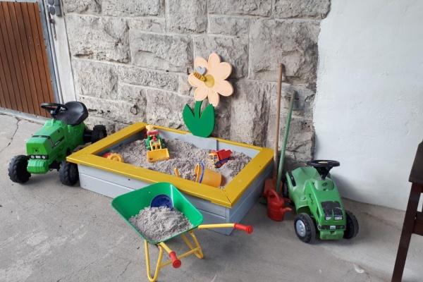 Tret-und Rutschfahrzeuge und ein zauberhafter Sandkasten warten auf die kleinen Gäste