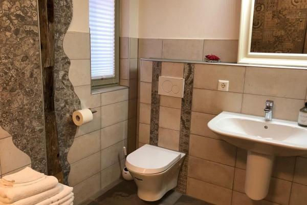 Auch im Bad zeigt sich altes Gebälk in Kombination mit zeitgemäßer Badkeramik
