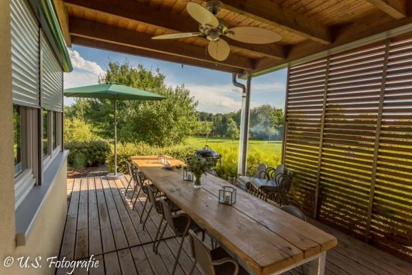 Auch im Außenbereich ein großer Tisch - windeschützt und überdacht