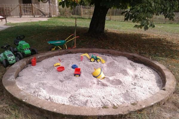 Tret-und Rutschfahrzeuge und ein Sandkasten warten auf die kleinen Gäste