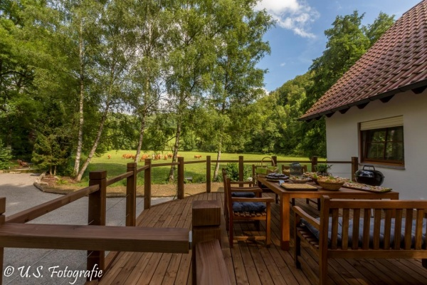 Die holzgedeckte Terrasse ist im Sommer das Outdoor-Esszimmer mit direktem Zugang zur Küche