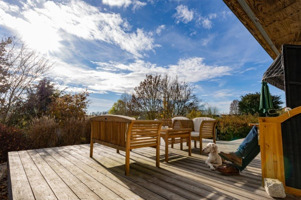 Die holzgedeckte Terrasse ist im Sommer das Outdoorzimmer